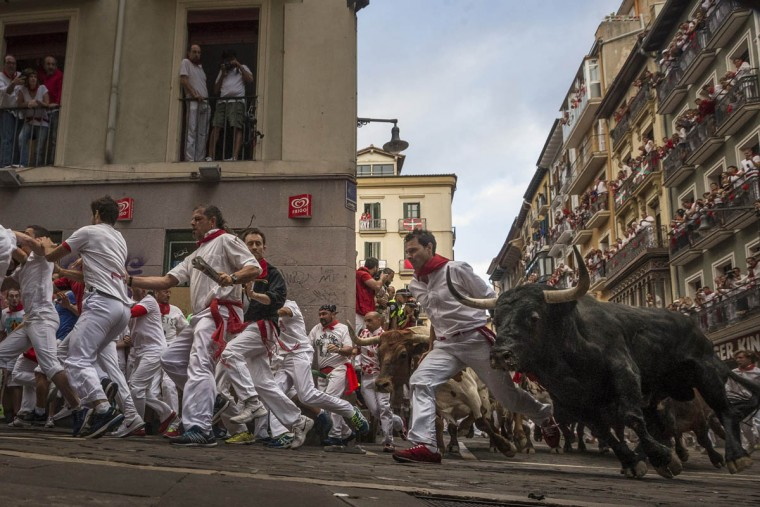 "Revelers are chased by a brave bull from the ""El Tajo y La Reina"" ranch as they turn Estafeta corner during a running of the bulls of the San Fermin festival. (Daniel Ochoa de Olza/AP photo)"