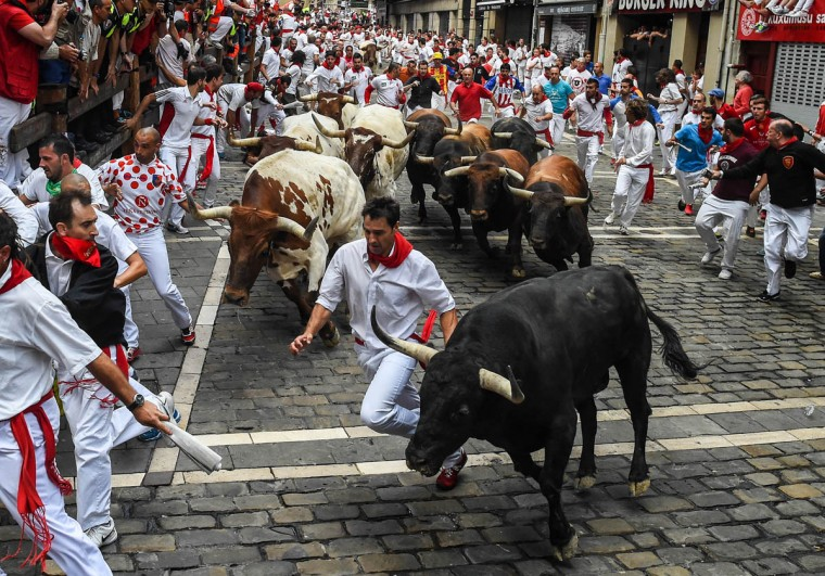 Revelers run with the Tajo and the Reina's fighting bulls entering Estafeta street during the third day of the San Fermin Running of the Bulls festival in Pamplona, Spain. (David Ramos/Getty Images)