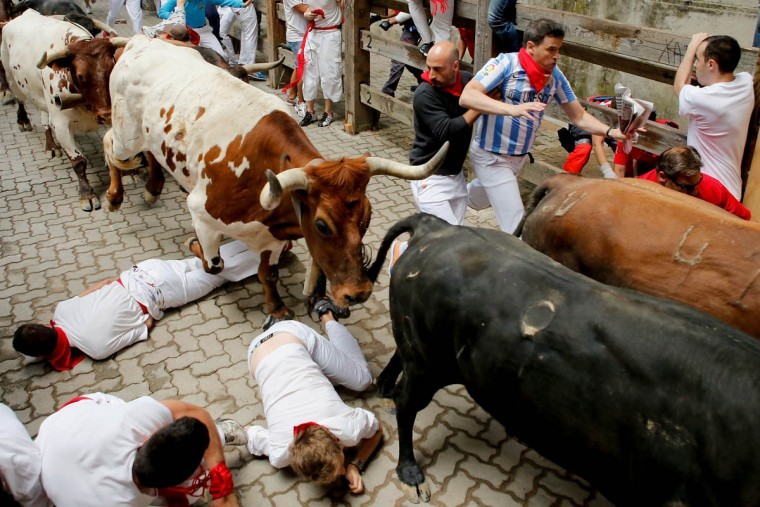 Revelers fall while running with the Tajo and the Reina's fighting bulls entering the bullring during the third day of the San Fermin Running Of The Bulls festival. (Pablo Blazquez Dominguez/Getty Images)
