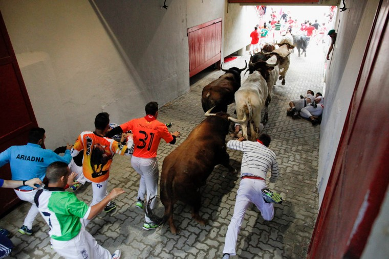 Revelers run with the Tajo and the Reina's fighting bulls entering the bullring during the third day of the San Fermin Running Of The Bulls festival. (Pablo Blazquez Dominguez/Getty Images)