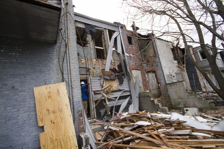 Details employees begin deconstructing the homes in the 900 block of N. Port Street. (Kalani Gordon, Baltimore Sun)