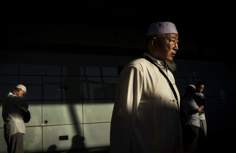 Chinese Hui Muslims wait as they prepare to board a flight to Saudi Arabia for a religious visit to Mecca and Medina during the holy fasting month of Ramadan, on July 2, 2014 at the Beijing International Airport in Beijing, China. There are more than 29 million members of the Hui Muslim minority in China. (Photo by Kevin Frayer/Getty Images)
