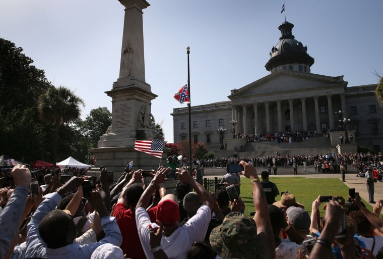 A crowd cheers as a South Carolina state police honor guard lowers the Confederate flag from the Statehouse grounds on July 10, 2015 in Columbia, South Carolina. Republican Governor Nikki Haley presided over the event after signing the historic legislation the day before. (Photo by John Moore/Getty Images)