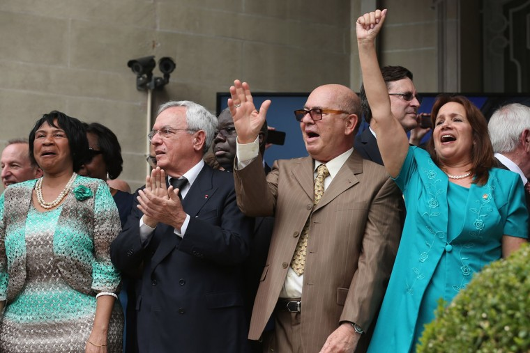"""Cuban Embassy employees shout """"Viva Cuba!"""" as the Cuban flag is raised in front of the building for the first time in 54 years July 20, 2015 in Washington, DC. The embassy was closed in 1961 when U.S. President Dwight Eisenhower severed diplomatic ties with the island nation after Fidel Castro took power in a Communist revolution. (Photo by Chip Somodevilla/Getty Images)"""