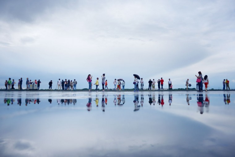 A group of tourists are reflected in water at the bank of Songhua River in Harbin, northeast China's Heilongjiang province on July 1, 2015. (WANG ZHAO/AFP/Getty Images)