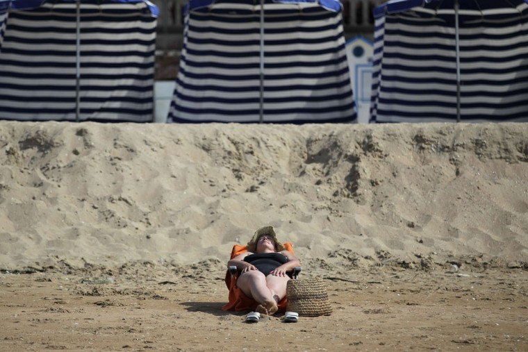 A woman sunbathes on the beach of the French northwestern city of Deauville on July 1, 2015, as a blistering heatwave sweeps through Europe with temperatures pushing 40 degrees Celsius. (CHARLY TRIBALLEAU/AFP/Getty Images)