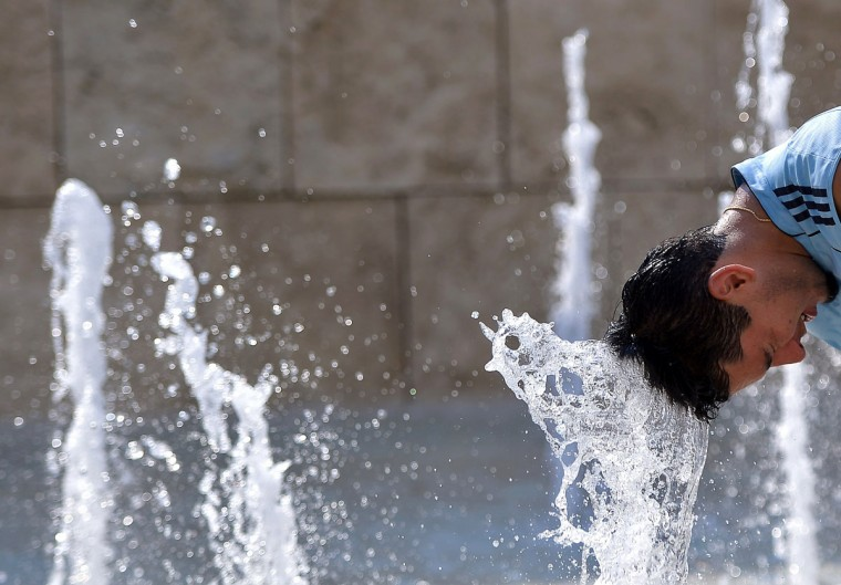 A tourist cools off in central Rome's Ara Pacis fountain on July 3, 2015 as a major heatwave spreads throughout Europe, with temperatures hitting nearly 40 degrees. (AFP Photo/Filippo Monteforte)