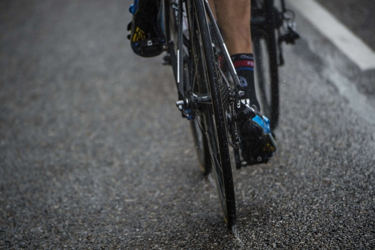 A cyclist rides in the rain during the 166 km second stage of the 102nd edition of the Tour de France cycling race on July 5, 2015, between Utrecht and Vrouwenpolder in Zeeland province, The Netherlands. (Lionel Bonaventure/AFP/Getty Images)