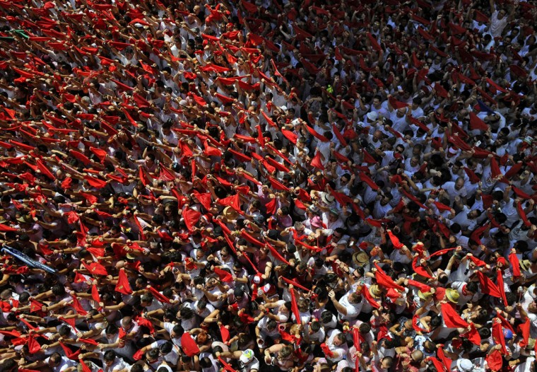Participants hold red scarves as they celebrate the 'Chupinazo' (start rocket) to mark the kickoff at noon sharp of the San Fermin Festival, in front of the Town Hall of Pamplona, northern Spain, on July 6, 2015. (MIGUEL RIOPA/AFP/Getty Images)