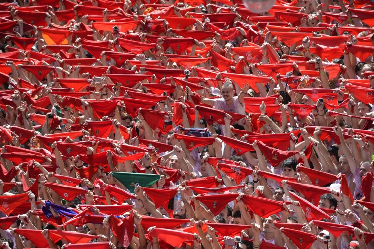 Revellers hold their red scarves as they celebrate the 'Chupinazo' (start rocket) to mark the kickoff at noon sharp of the San Fermin Festival, in front of the Town Hall of Pamplona, northern Spain, on July 6, 2015. (MIGUEL RIOPA/AFP/Getty Images)