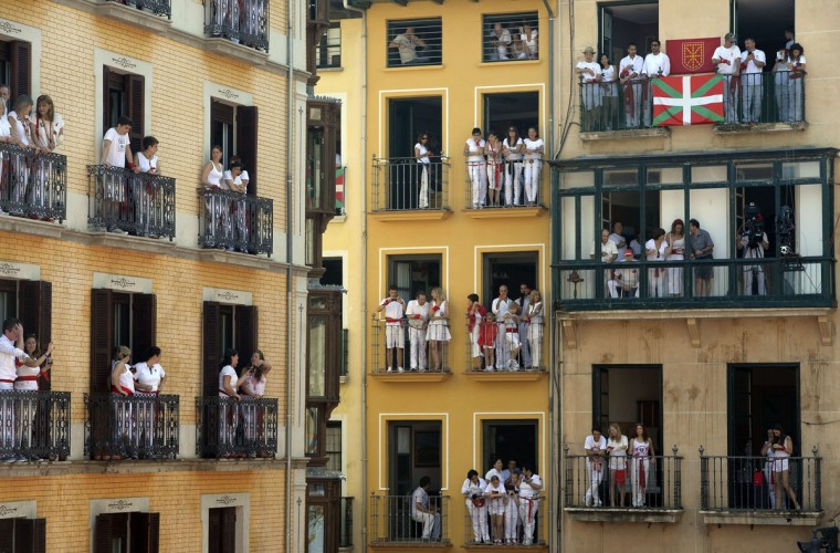 People on balconies witness the 'Chupinazo' (start rocket) celebration that marks the kickoff at noon sharp of the San Fermin Festival, in front of the Town Hall of Pamplona, northern Spain, on July 6, 2015. A red-and-white sea of revelers soaked each other with wine in a packed Pamplona square today to start off Spain's most famous fiesta, the San Fermin bull-running festival. (MIGUEL RIOPA/AFP/Getty Images)