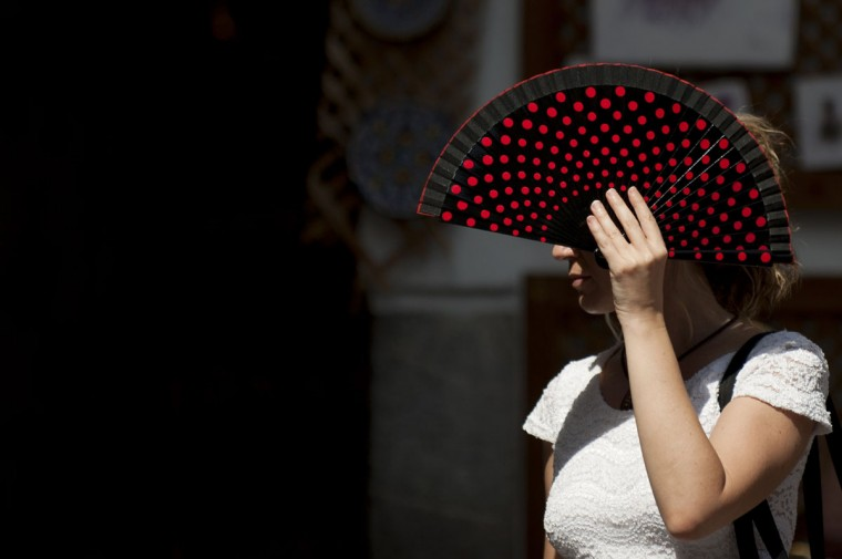 A woman uses a fan to protect herself from the sun in Cordoba on July 7, 2015. In Spain started on July 1, 2015 a new heatwave which will last for at least nine days and extend to the rest of Europe. The heatwave, the second of the summer, will affect almost all of Spain. (AFP Photo/P / )