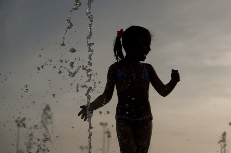 A girl cools off in a fountain in Cordoba on July 7, 2015. In Spain started on July 1, 2015 a new heatwave which will last for at least nine days and extend to the rest of Europe. The heatwave, the second of the summer, will affect almost all of Spain. (AFP Photo/P / )