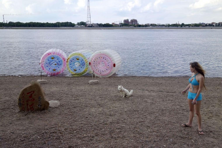 This picture taken on July 4, 2015 shows a Russian woman walking her dog on the banks of the Heilongjiang River in the border city of Heihe, northeastern China's Heilongjiang province. The warmth of the friendship between Chinese President Xi Jinping and Russia's Vladimir Putin -- who meet July 8 for the eighth time in two years -- does little to counter the bitter economic winds blowing through their shared border. (WANG ZHAO/AFP/Getty Images)