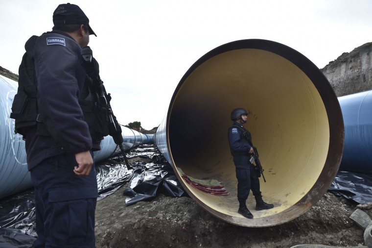 "Federal policemen inspect a pipe under construction by the Altiplano prison in Almoloya de Juarez, Mexico on July 12, 2015. Mexican drug lord Joaquin ""El Chapo"" Guzman has escaped from a maximum-security prison, the government said Sunday, his second jail break in 14 years. The kingpin was last seen in the shower area of the Altiplano prison in central Mexico late Saturday before disappearing. ""The escape of Guzman was confirmed"", the National Security Commission said in a statement. (Yuri Cortez/AFP/Getty Images)"