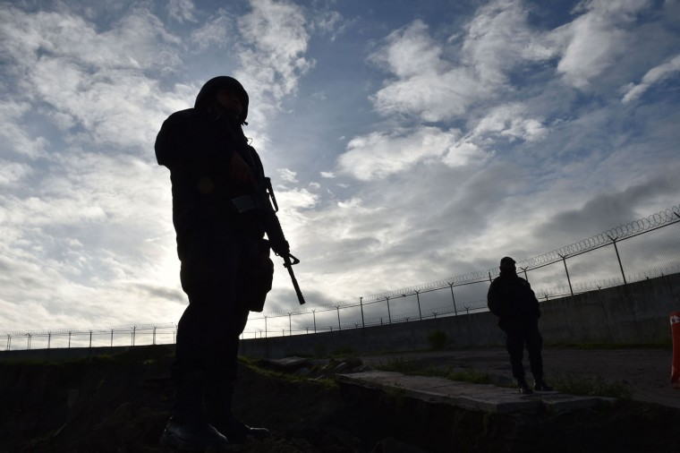 "Federal policemen stand guard outside the Altiplano prison in Almoloya de Juarez, Mexico on July 12, 2015. Mexican drug lord Joaquin ""El Chapo"" Guzman has escaped from a maximum-security prison, the government said Sunday, his second jail break in 14 years. The kingpin was last seen in the shower area of the Altiplano prison in central Mexico late Saturday before disappearing. ""The escape of Guzman was confirmed"", the National Security Commission said in a statement. (Yuri Cortez/AFP/Getty Images)"