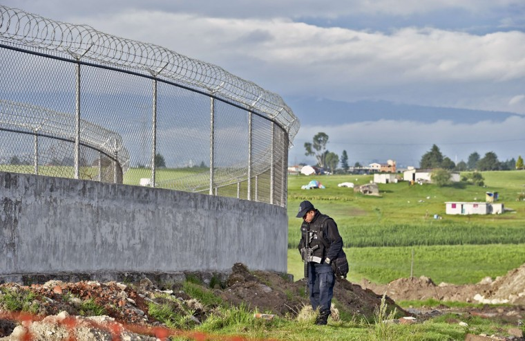 "A policeman searches outside the Altiplano prison in Almoloya de Juarez, Mexico on July 12, 2015. Mexican drug lord Joaquin ""El Chapo"" Guzman has escaped from a maximum-security prison, the government said Sunday, his second jail break in 14 years. The kingpin was last seen in the shower area of the Altiplano prison in central Mexico late Saturday before disappearing. ""The escape of Guzman was confirmed"", the National Security Commission said in a statement. (Yuri Cortez/AFP/Getty Images)"