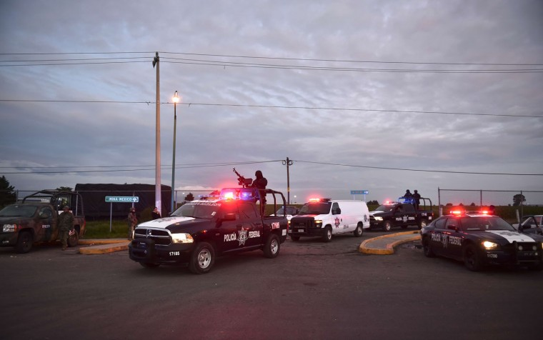 "Federal police escort a convoy transporting alleged drug traffickers from the Altiplano prison in Almoloya de Juarez, Mexico on July 12, 2015. Mexican drug lord Joaquin ""El Chapo"" Guzman has escaped from a maximum-security prison, the government said Sunday, his second jail break in 14 years. The kingpin was last seen in the shower area of the Altiplano prison in central Mexico late Saturday before disappearing. ""The escape of Guzman was confirmed"", the National Security Commission said in a statement. (Yuri Cortez/AFP/Getty Images)"