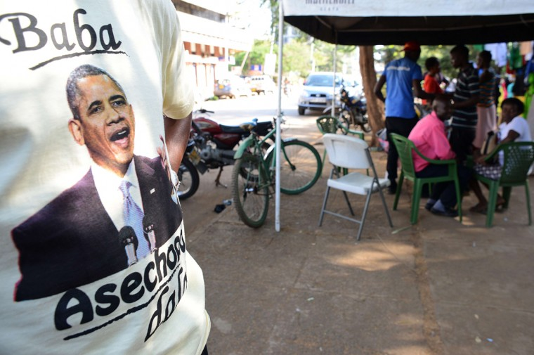 "Kenyan vendor Hosea displays his t-shirts with a depiction of US President Barack Obama at the Kogelo market on July 13, 2015 in Kisumu. Excitement is growing in Kenya ahead of Barack Obama's first visit to his father's homeland since becoming president. Anticipation ahead of the late July trip is nowhere greater than in Kogelo, ""a sleepy village"" that was ""put on the world map"" by its association with the US president, according to his uncle Said Obama. (Simon Maina/AFP/Getty Images)"