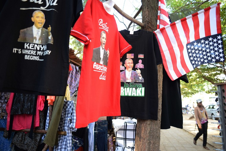 "A woman buys glasses next to a shop selling t-shirts with a depiction of US President Barack Obama at the Kogelo market on July 13, 2015 in Kisumu. Excitement is growing in Kenya ahead of Barack Obama's first visit to his father's homeland since becoming president. Anticipation ahead of the late July trip is nowhere greater than in Kogelo, ""a sleepy village"" that was ""put on the world map"" by its association with the US president, according to his uncle Said Obama. (Simon MainaAFP/Getty Images)"