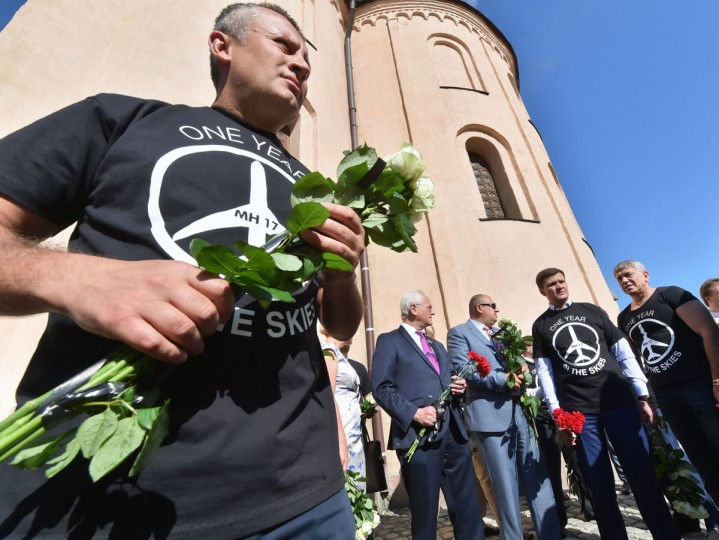 "People wearing t-shirts bearing a drawing of a plane and slogans reading "" MH 17, One year in the skies"" hold flowers to the Dutch embassy in Kiev on July 17, 2015 in memory of the people who died in the crash of Malaysian Airlines flight MH17. All 298 passengers and crew -- the majority Dutch -- died on July 17 last year when the Malaysia Airlines Boeing 777, on a flight between Amsterdam and Kuala Lumpur, was shot down over rebel-held east Ukraine during heavy fighting between Ukrainian forces and pro-Russian separatists. (AFP Photo/P / )"