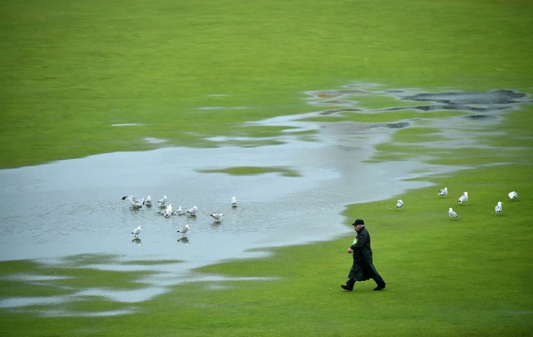 Gulls enjoy the water-logged 1st fairway as a course official walks past after heavy rain make the course unplayable early on the second day of the 2015 British Open Golf Championship on The Old Course at St Andrews in Scotland, on July 17, 2015. By 8:00 p.m. large puddles had formed on the Old Course's fairways and greens as the deluge continued and director of greenkeeping Gordon Moir said that no time could yet be set for play to resume. (AFP Photo/Ben Stansall)