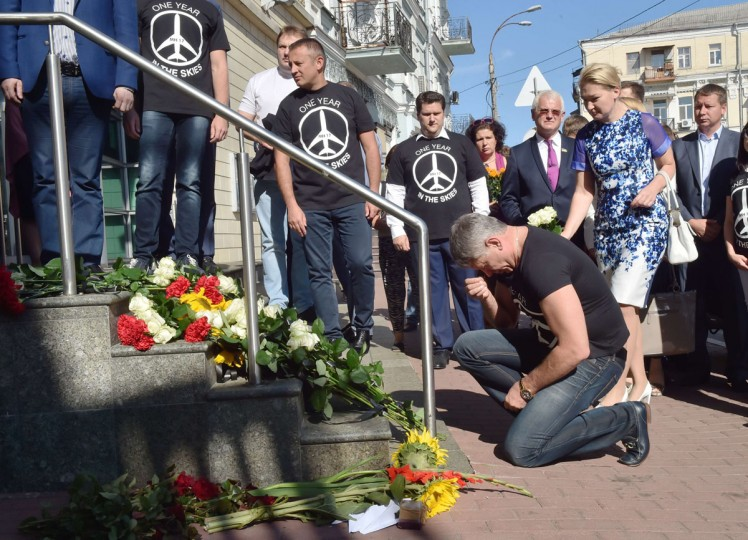 A man kneels down in front of flowers laid in front of the Dutch embassy in Kiev on July 17, 2015 in memory of the people who died in the crash of Malaysian Airlines flight MH17. All 298 passengers and crew -- the majority Dutch -- died on July 17 last year when the Malaysia Airlines Boeing 777, on a flight between Amsterdam and Kuala Lumpur, was shot down over rebel-held east Ukraine during heavy fighting between Ukrainian forces and pro-Russian separatists. (AFP Photo/P / )