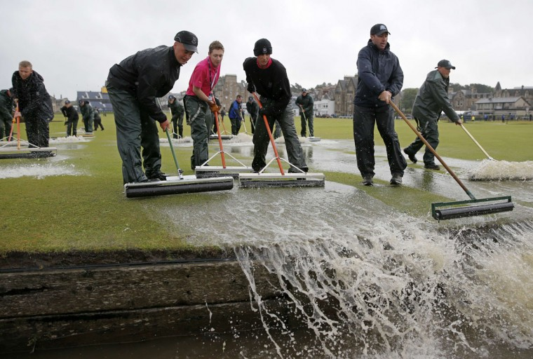 Groundsmen sweep water into the Swilcan Burn from the 1st fairway, after heavy rain make the course unplayable early on the second day of the 2015 British Open Golf Championship on The Old Course at St Andrews in Scotland, on July 17, 2015. By 8:00 p.m. (0700GMT) large puddles had formed on the Old Course's fairways and greens as the deluge continued and director of greenkeeping Gordon Moir said that no time could yet be set for play to resume. (AFP Photo/Adrian Dennis)