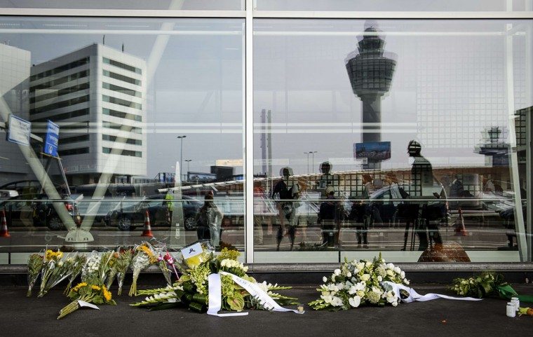 People are reflected in a window, as the stand in front of flowers laid at the departure hall 3, at the airport in Schiphol, the Netherlands, on July 17, 2015, in memory of the people who died in the crash of Malaysian Airlines flight MH17 a year ago. All 298 passengers and crew -- the majority Dutch -- died on July 17 last year when the Malaysia Airlines Boeing 777, on a flight between Amsterdam and Kuala Lumpur, was shot down over rebel-held east Ukraine during heavy fighting between Ukrainian forces and pro-Russian separatists. (AFP Photo/Anp / )
