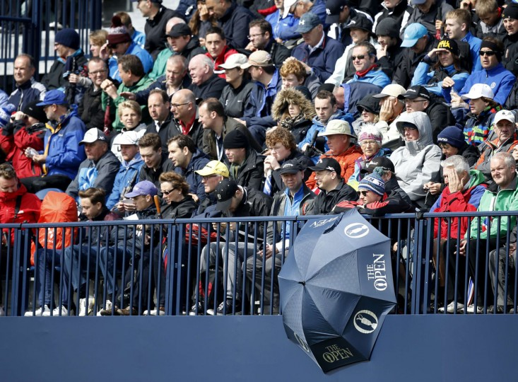 Spectators in a grandstand watch play in the morning sunshine on day two of the 2015 British Open Golf Championship on The Old Course at St Andrews in Scotland, on July 17, 2015. Torrential early rain left its mark on the Old Course at St Andrews as play was suspended for more than three hours and continued to have an effect when play restarted. The delay may mean that the later starters will be unable to complete their second round by day's end. (AFP Photo/Adrian Dennis)