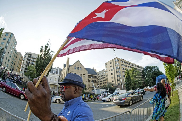 A man waves the US and Cuban flags as he walks in front of the new Cuban Embassy shortly before it's official ceremonial opening July 20, 2015, in Washington, DC. The United States and Cuba formally resumed diplomatic relations on July 20, as the Cuban flag was raised at the US State Department in a historic gesture toward ending decades of hostility between the Cold War foes. (AFP Photo/P /paul )