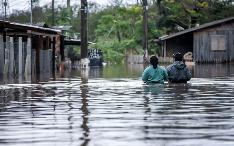 A couple wades through the streets of the flooded neighborhood of Vila Rica, in Gravatai, southern Brazil, on July 21, 2015.(JEFFERSON BERNARDES/AFP/Getty Images)