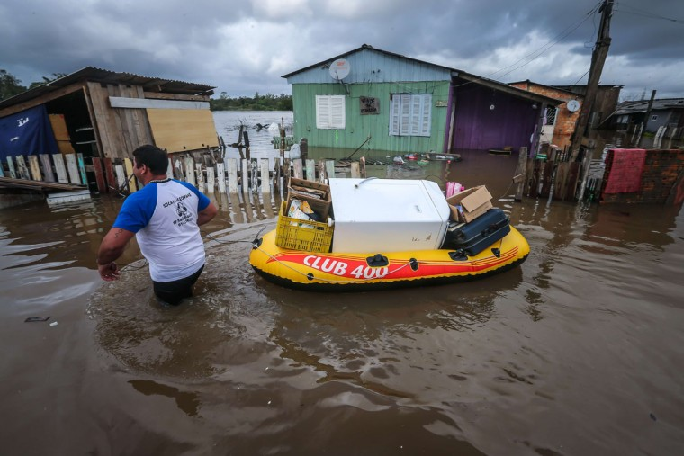 A man carries some belongings on an inflatable boat as he wades through the streets of the flooded neighborhood of Vila Rica, in Gravatai, southern Brazil, on July 21, 2015. (JEFFERSON BERNARDES/AFP/Getty Images)
