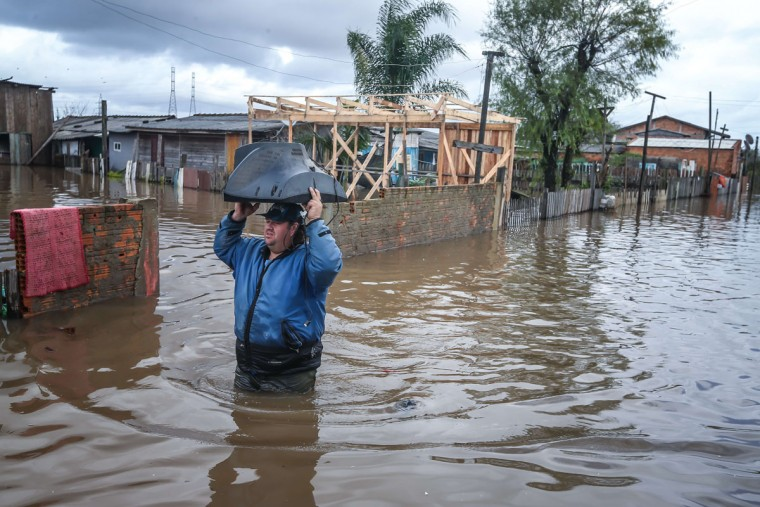 A local resident carrying a television set wades along a flooded street in Villa Rica, Gravatai, Brazil, on July 21, 2015.(JEFFERSON BERNARDES/AFP/Getty Images)