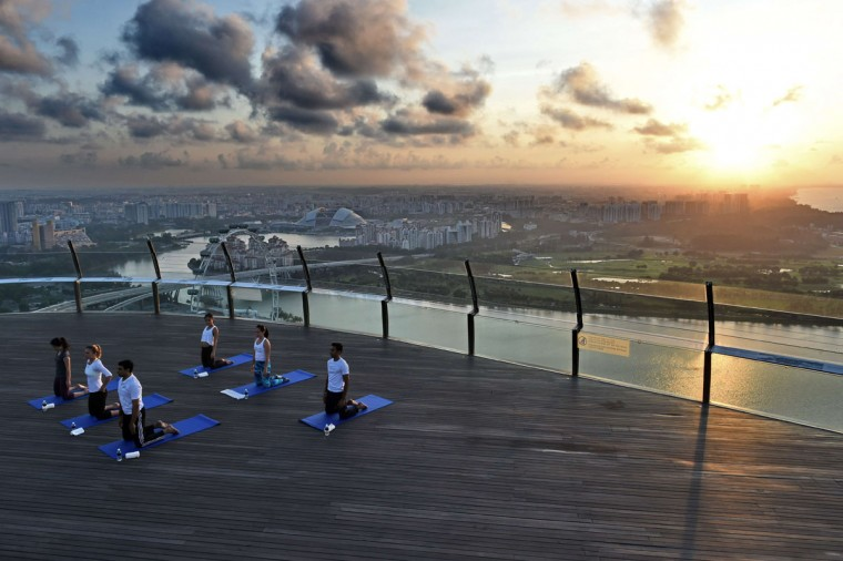 World number three tennis player Simona Halep of Romania (2nd left) takes part in a yoga session at skypark observation deck at the top of the Marina Bay Sands in Singapore on July 22, 2015. (ROSLAN RAHMAN/AFP/Getty Images)