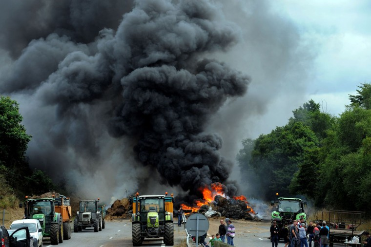 Farmers use tractors and burn tires, hay and manure as they block the highway between Morlaix and Brest during a demonstration against the market prices of their product, on July 22, 2015 in Morlaix, western of France. French farmers protesting over falling food prices threatened to step up blockades of cities, roads and tourist sites, as the government prepared to unveil emergency aid for them. Farmers have dumped manure in cities, blocked access roads and motorways and hindered tourists from reaching Mont St-Michel in northern France, one of France's most visited sites. (FRED TANNEAU/AFP/Getty Images)