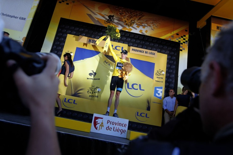 Britain's Christopher Froome, wearing the overall leader's yellow jersey, celebrates on the podium of the third stage of the Tour de France cycling race over 159.5 kilometers (99.1 miles) with start in Antwerp and finish in Huy, Belgium, Monday, July 6, 2015. (AP Photo/Laurent Cipriani)
