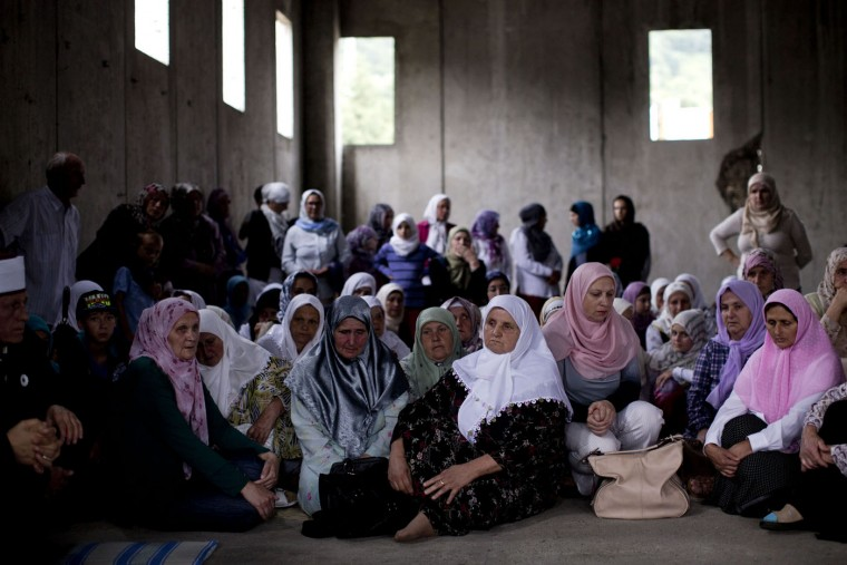 People pause before praying at the Potocari memorial complex, close to Srebrenica, 150 kilometers northeast of Sarajevo, Bosnia and Herzegovina, Thursday, July 9, 2015. The 20th anniversary of the Srebrenica massacre, the worst crime in Europe after the Nazi era, will be marked on Saturday, July 11, 2015. (AP Photo/Marko Drobnjakovic)