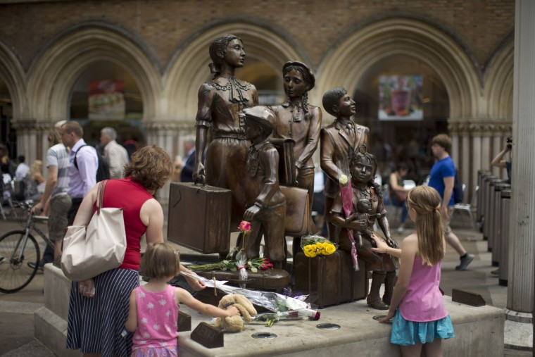 "People look at flowers laid in memory of Britain's Sir Nicholas Winton on German-born Jewish sculptor Frank Meisler's ""Kindertransport"" (German for children transport) memorial statue outside Liverpool Street Station in London, Thursday, July 2, 2015. Winton, a humanitarian who almost single-handedly saved more than 650 Jewish children from the Holocaust, earning himself the label ""Britain's Schindler,"" has died aged 106. Winton arranged trains to carry children from Nazi-occupied Prague to Britain, battling bureaucracy at both ends and saving them from almost certain death. (AP Photo/Matt Dunham)"