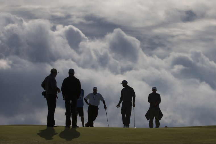 Tiger Woods of the United States, second right, walks across the 11th green during a practice round at St Andrews Golf Club prior to the start of the British Open Golf Championship, in St. Andrews, Scotland, Monday, July 13, 2015. (AP Photo/Jon Super)