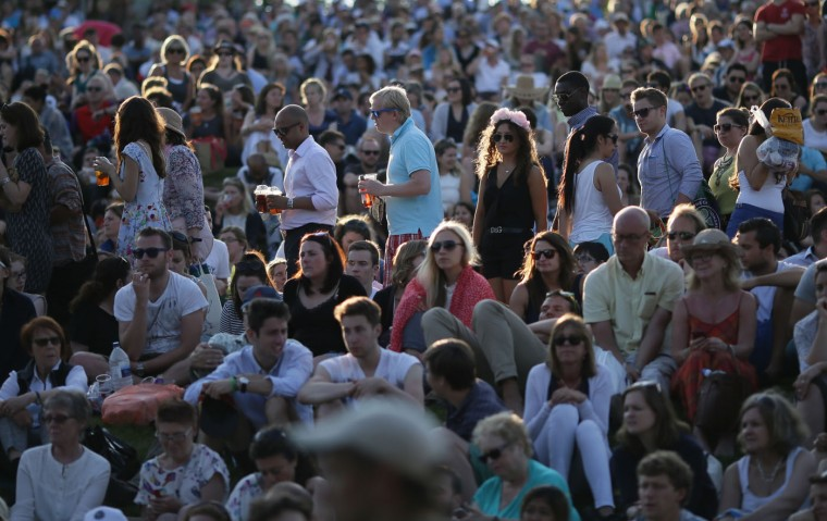 Spectators watch the singles match between Dustin Brown of Germany and Rafael Nadal of Spain on the big screen on Murray Mount at the All England Lawn Tennis Championships in Wimbledon, London, Thursday July 2, 2015. (AP Photo/Tim Ireland)