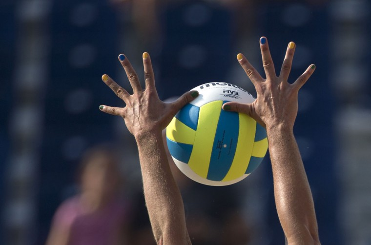 Brazil's Liliane Maestrini, with her fingernails painted in the colors of the national flag, blocks the ball, during Brazil's beach volleyball preliminary match against Nicaragua at the Pan Am Games in Toronto, Monday, July 13, 2015. (AP Photo/Rebecca Blackwell)