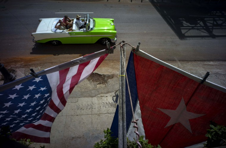 A U.S., and a Cuban national flag, hang from a balcony to mark the restored full diplomatic relations between Cuba and the Unites States, in Old Havana, Monday, July 20, 2015. The new era began with little fanfare when an agreement between the two nations to resume normal ties on July 20 came into force just after midnight Sunday and the diplomatic missions of each country were upgraded from interests sections to embassies. (AP Photo/Ramon Espinosa)