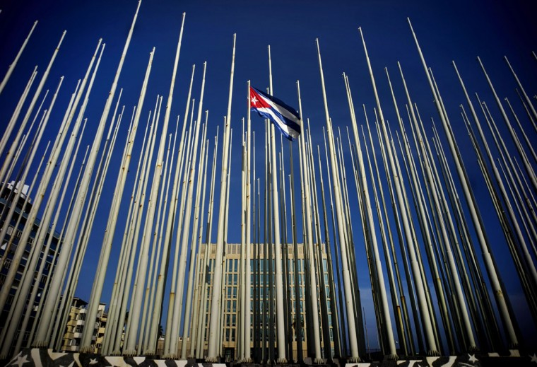 A Cuban flag flies among empty flag polls near the U.S. Interests Section building, behind, in Havana, Sunday, July 19, 2015. Washington and Havana plan to officially restore diplomatic relations on Monday with the reopening of their embassies. While no formal ceremony is planned Monday for the U.S. Interests Section in Havana, it too will become a full-fledged embassy just after midnight as the Cold War foes formally enter a new era of engagement. (AP Photo/Ramon Espinosa)