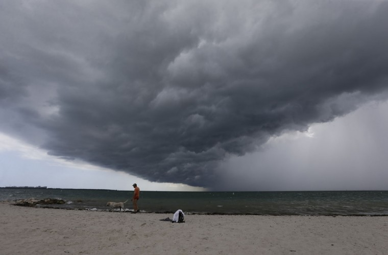 Arnie Powell walks along the beach with his pet dog, Biscuit, as rain clouds approach Hobie Beach, Wednesday, July 22, 2015, in Key Biscayne, Fla. (AP Photo/Alan Diaz)