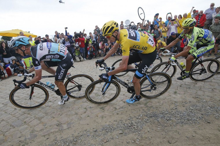Stage winner Germany's Tony Martin, left, Britain's Christopher Froome, wearing the overall leader's yellow jersey, and Spain's Alberto Contador, right, ride on a cobblestone sector during the fourth stage of the Tour de France cycling race over 223.5 kilometers (138.9 miles) with start in Seraing, Belgium, and finish in Cambrai, France, Tuesday, July 7, 2015. (AP Photo/Christophe Ena)