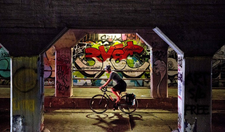 A bicyclist passes through the Krog Street Tunnel Wednesday, July 15, 2015, in Atlanta. The tunnel runs under train tracks carrying freight cars and is known for its urban street art. Connecting the eclectic neighborhoods of Cabbagetown and Inman Park, the tunnel also serves as a message board with frequently updated posts about local events and shows. (AP Photo/David Goldman)