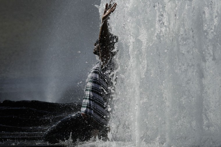A man cools off in a fountain in Berlin, Thursday, July 2, 2015. A mass of hot air moving north from Africa has sent temperatures spiking in Spain, Portugal, Britain, France and Germany in recent days. Temperatures in Germany are expected to reach up to 38 degrees Celsius (100 degrees Fahrenheit) on Thursday. (AP Photo/Markus Schreiber)