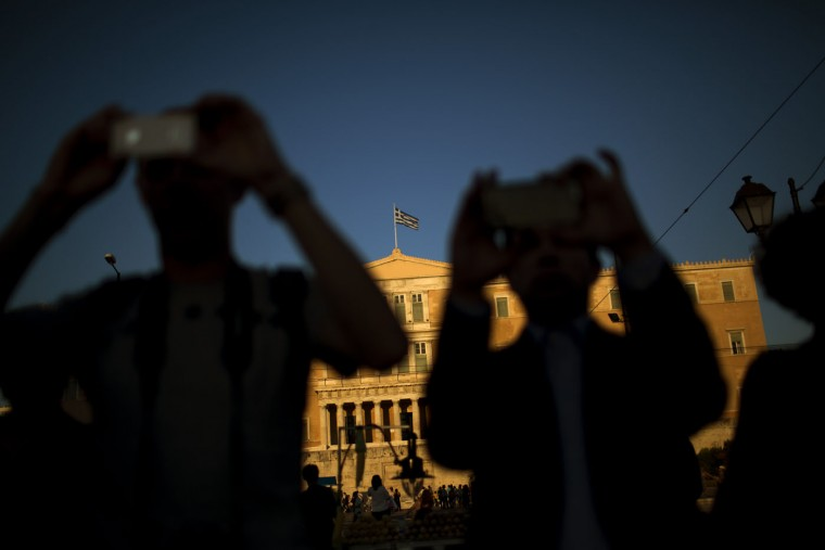 People take photos as demonstrators from the Greek Communist party gather during a rally supporting the no vote for the upcoming referendum in front of the parliament in Athens, Thursday, July 2, 2015. The battle for Greek votes entered full swing Thursday ahead of a crucial weekend referendum that could decide whether the country falls out of the euro. (AP Photo/Emilio Morenatti)