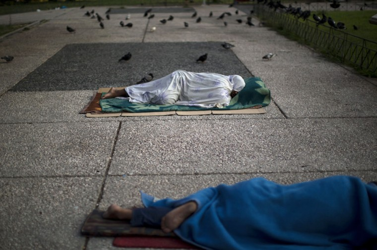 """Homeless sleep on the ground in central Athens, Monday, July 6, 2015. Greece's finance minister has resigned following Sunday's referendum in which the majority of voters said """"no"""" to more austerity measures in exchange for another financial bailout. (AP Photo/Emilio Morenatti)"""